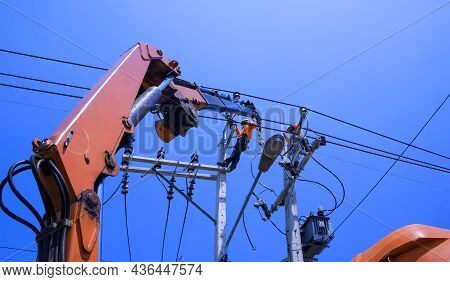 Low Angle View Of Two Electricians With Crane Truck Are Working To Install Electrical Transmission O