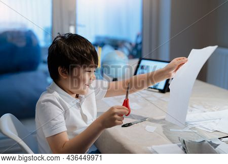 Kid Using Scissors Cutting White Paper, Schoolboy Making Art And Craft For His Homework,child Learni