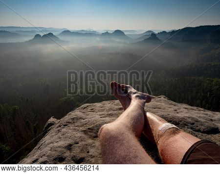 Crossed Male Barefoot Legs Of Man Relax On Mountain Summit. Hiker Lay Down And Have A Rest