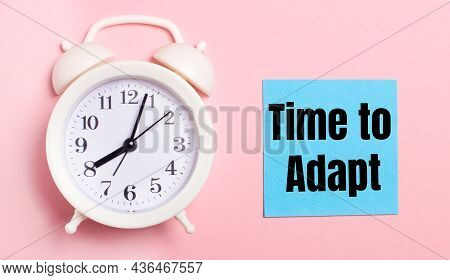 On A Light Pink Background, A White Alarm Clock And A Blue Sheet Of Paper With The Text Time To Adap