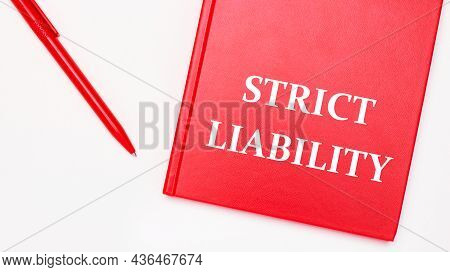 The Text Strict Liability Is Written On A Red Notepad Near A Red Pen On A White Table In The Office.