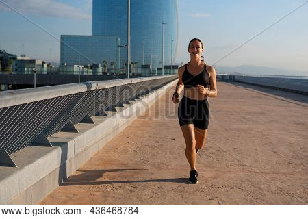 Happy Sportswoman In Black Activewear Smiling And Looking At Camera While Jogging On Embankment Earl