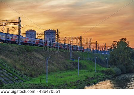 Suburban Electric Train On The Embankment During Sunset