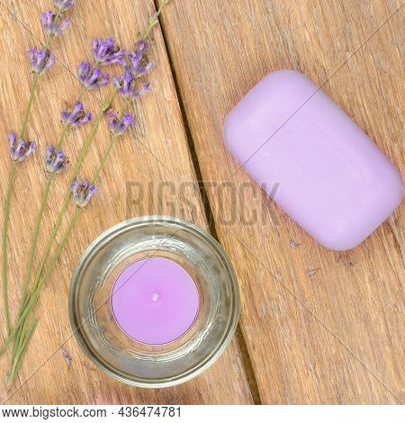 Lavender Flowers, Soap And Scented Candle On A Wooden Background. Beauty And Spa Products.
