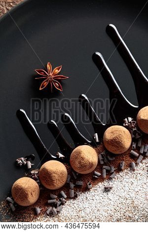 Chocolate Truffles On A Black Plate With Chocolate Sauce. Sweets Are Sprinkled With Cocoa Powder And