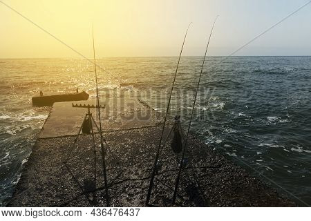 Three Fishing Rods Are Set On The Pier With The Sea In The Background. The Concept Of Waiting For A