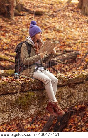 Woman Relaxing Outdoors On A Sunny Autumn Day, Sitting In The Forest While Taking A Hiking Break, Re