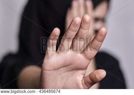 A Muslim Woman In Traditional Black Clothing Nikab Showing Stop Hand Gesture. Role Of Women In Islam