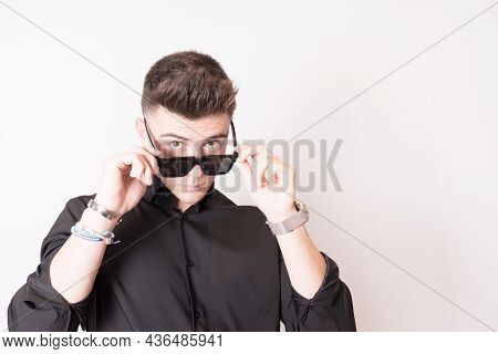 Studio Shot Of An Attractive Young Man In Black Wearing Sunglasses. White Background. Copy Space
