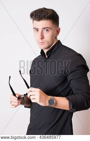 Studio Shot Of A Young Man With Sunglasses On His Hands.white Background