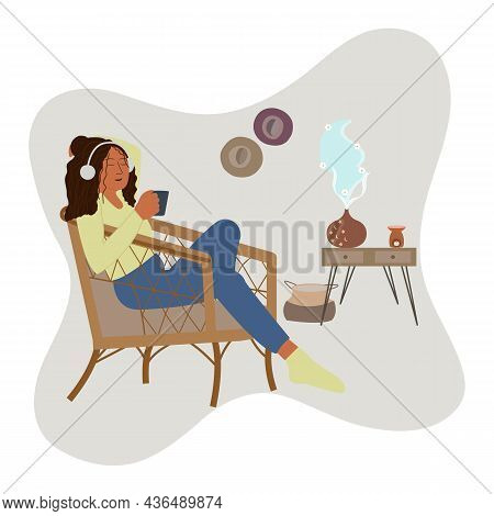 Young Woman Drinks Tea And Listening Music On Headphone Sitting On Armchair At Cozy Home While Enjoy