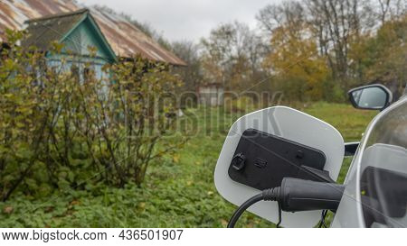 White Electric Car Is Charged In The Village. Outside The City The Countryside. Private Electric Car