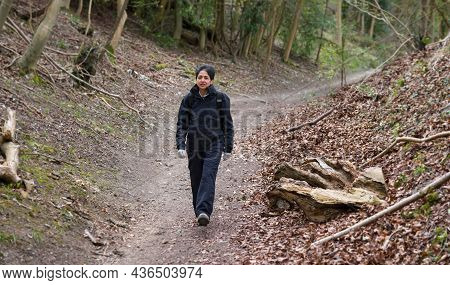 British Asian Indian Woman Hiking Alone In Winter Through Woodland Or Forest On A Footpath In Englis