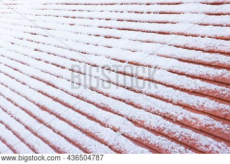 Closeup Of Plain Clay Roof Tiles Covered In Snow In Winter, Uk