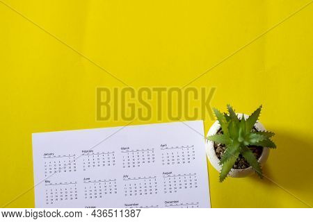 Top View Calendar Place On Yellow Desk. Desktop Calender For Planner To Plan Agenda, Timetable, Appo