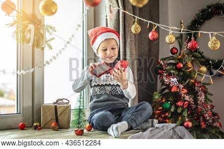 Cute Little Boy In A Red Santa Hat Is Sitting By The Window In A Decorated Room And Looking Inside A