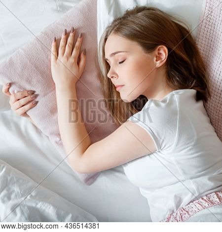 Young Woman Sleeping In Bed. Portrait Of Blonde Teen Girl Have Healthy Good Sleep On White Pink Pill