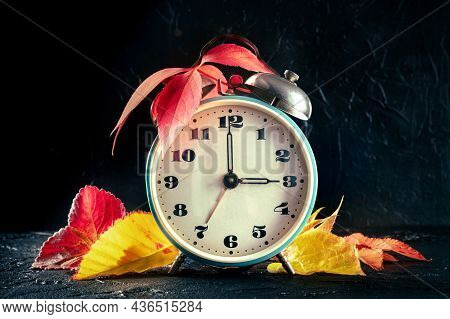 Daylight Saving Time Concept, Fall Back In Autumn. A Vintage Alarm Clock With Autumn Leaves On A Bla