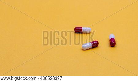 Red-white Antibiotic Capsule Pills On Yellow Background. Prescription Drug. Antibiotic Drug Resistan