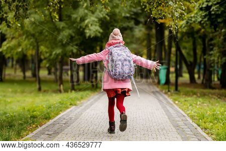 School girl with backpack running at autumn park. Preteen child having fun oudoors