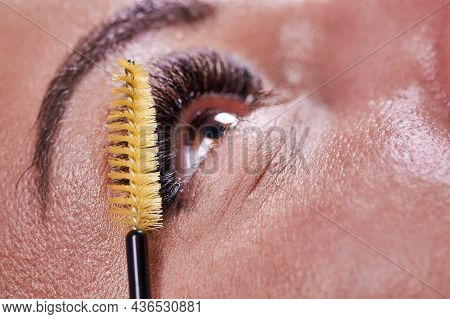 Close Up Of Female Eye With Beautiful Long Eyelashes And Yellow Mascara Brush. Young Woman With Perf