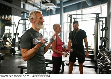 Side View Cheerful Elderly Man Excercising With Dumbbells Next To His Attractive Wife. Mature Sporty