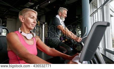 Close Portrait Of Sporty Senior Couple Excercising On Bikes In Gym. Attractive Mature Woman With Sho
