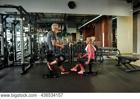 Two Happy Senior Man And Woman In Gym, Talking While Break Time. Attractive Fit Woman Holding Bottle