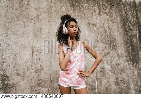 Young black sportswoman in headphones measuring her pulse while standing by concrete wall