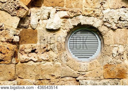 Round Plastic Ventilation Grate In The Stone Wall. High Quality Photo