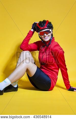 Cycling Ideas. Portrait Of Positive Female Road Cyclist In Professional Outfit Sitting On Floor Agai