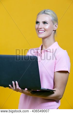 Portrait Of Smiling Caucasian Blond Girl With Laptop Posing With Smile Against Colorful Yellow Backg