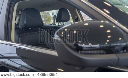 Close-up Front View Of Rearview Mirror And Modern Car Interior. A Rear View Mirror On A Car Door. Ne