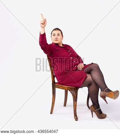 Full Length Of Contented Businesswoman, Sitting On Chair, Pointing Forefinger Looking Up, Showing Di