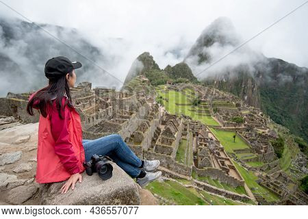 Young Asian Woman Traveler Looking At Machu Picchu, One Of Seven Wonders And Famous Tourist Attracti