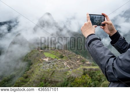Male Tourist Taking Photo Of Machu Picchu On Smartphone, One Of Seven Wonders And Famous Tourist Att