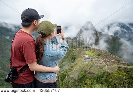 Asian Couple Tourist Taking Photo Of Machu Picchu On Smartphone, One Of Seven Wonders And Famous Tou