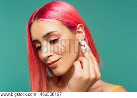 Young Woman With Pink Dyed Hair Holding Wireless Earphone Isolated On Blue