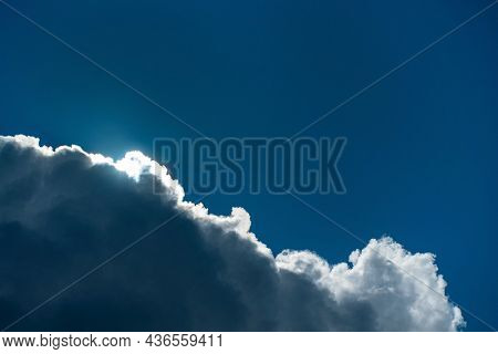 Download PreviewShareAdd to LikeboxCloudscape with the sun shining through the clouds in a blue sky.