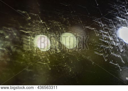 Night Unfocused View Through Wet Glass With Raindrops On The Background Of Street Lights, Blurred Ba