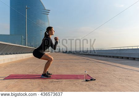 Side View Of Female Athlete In Black Activewear Clasping Hands And Doing Squats On Mat During Fitnes