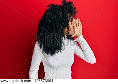 African american woman with afro hair wearing casual sweater and glasses shouting and screaming loud to side with hand on mouth. communication concept.