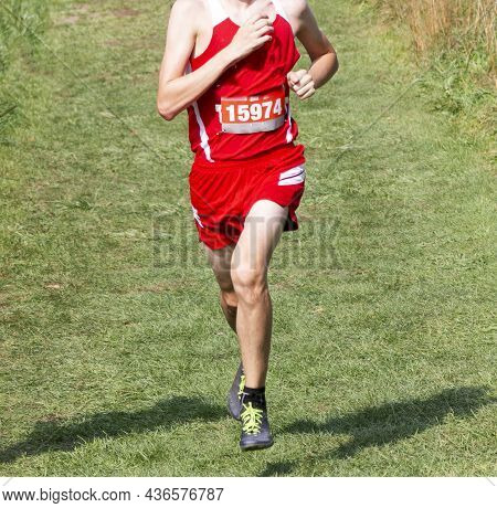 Front View Of A High School Boy Running A 5k Race On A Grass Field Downhill.
