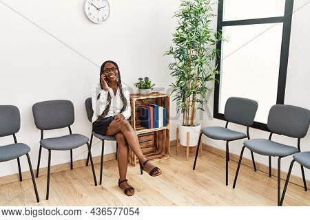 Young african american woman talking on the smartphone at waiting room.