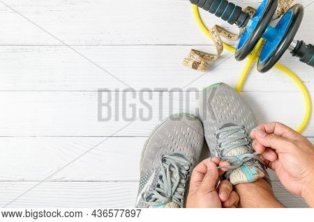 Man Hand Tie Shoelaces His Training Shoe With Abdominal Exercises And Waist Tape On A White Wood Bac