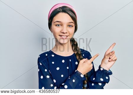 Young brunette girl wearing elegant look smiling and looking at the camera pointing with two hands and fingers to the side.