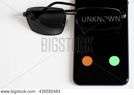 Smartphone With An Unknown Call Lies On A White Table Next To Sunglasses. The Problem Of The Safety