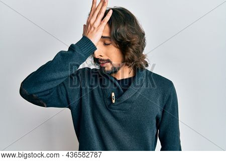 Young hispanic man wearing casual clothes surprised with hand on head for mistake, remember error. forgot, bad memory concept.