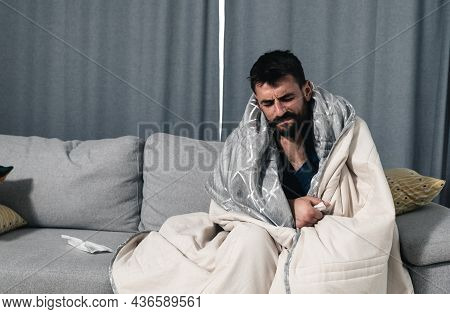 Young Man Feeling Sick With Cold And Fever At Home, Ill With Flu Virus Disease Sitting On The Sofa W
