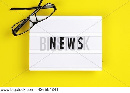 News Word On Lightbox With Eyeglases On Yellow Background, Flat Lay